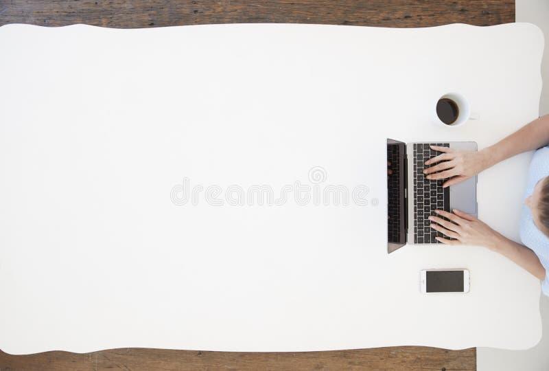 Sammanträde för ung kvinna på ett skrivbord och maskinskrivning på bärbar datordatoren royaltyfri foto