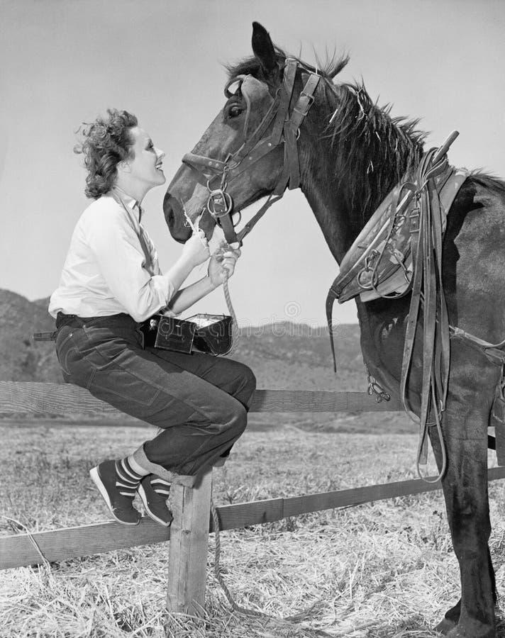 Sammanträde för ung kvinna på ett staket och matning av hennes häst (alla visade personer inte är längre uppehälle, och inget god royaltyfria foton