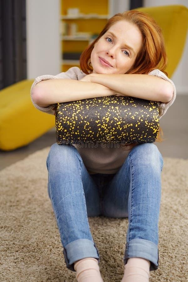 Sammanträde för ung kvinna på golv med skumrullen arkivfoto