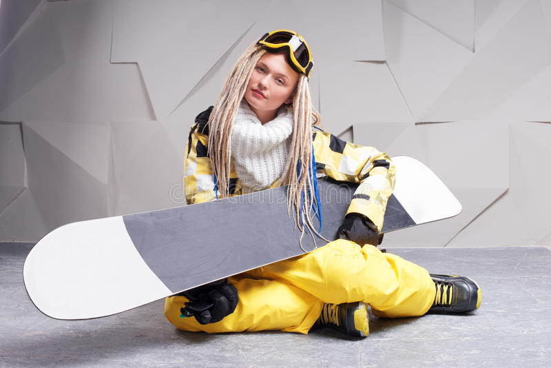 Sammanträde för ung kvinna på golv med snowboarden arkivfoto