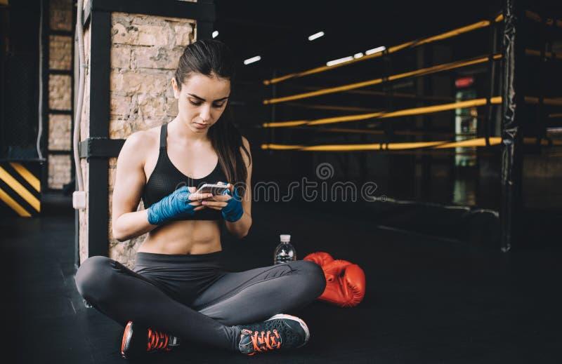 Sammanträde för ung kvinna på golvet efter hård genomkörare i idrottshall royaltyfri foto