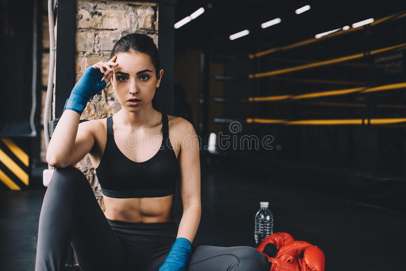 Sammanträde för ung kvinna på golvet efter hård genomkörare i idrottshall royaltyfri fotografi