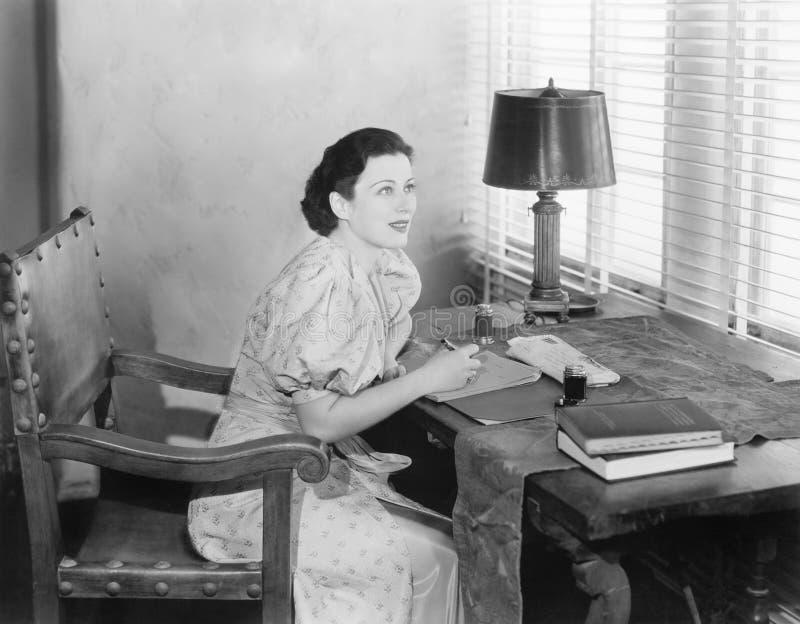 Sammanträde för ung kvinna på hennes skrivbord som skrivar ett brev (alla visade personer inte är längre uppehälle, och inget god fotografering för bildbyråer