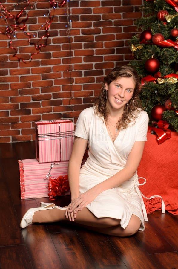 Sammanträde för ung kvinna på julträdet arkivfoto