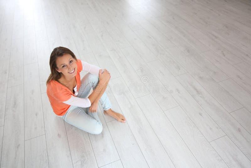 Sammanträde för ung kvinna på koppla av för golv royaltyfria foton