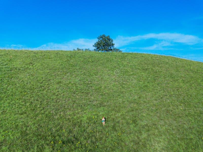 Sammanträde för ung kvinna på kullen som tycker om naturen arkivbilder
