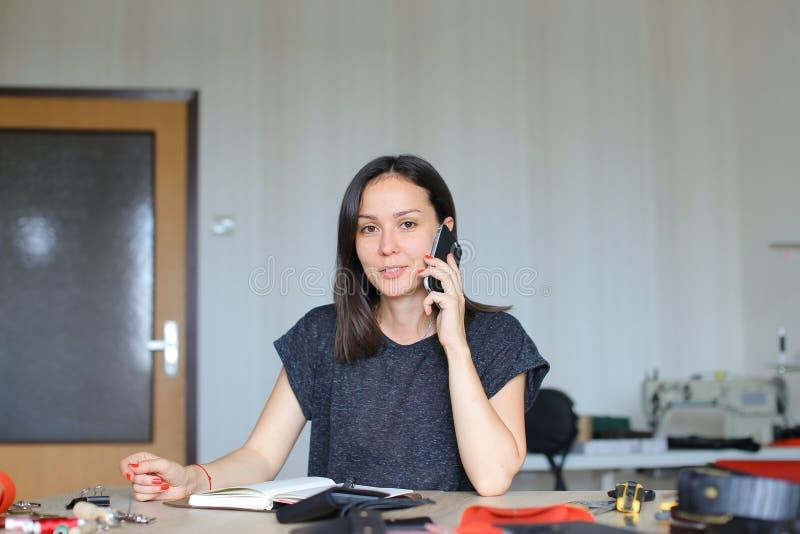Sammanträde för ung kvinna på läderatelieren och anteckningsboken och plånböcker för danande som den handgjorda talar vid smartph arkivbild