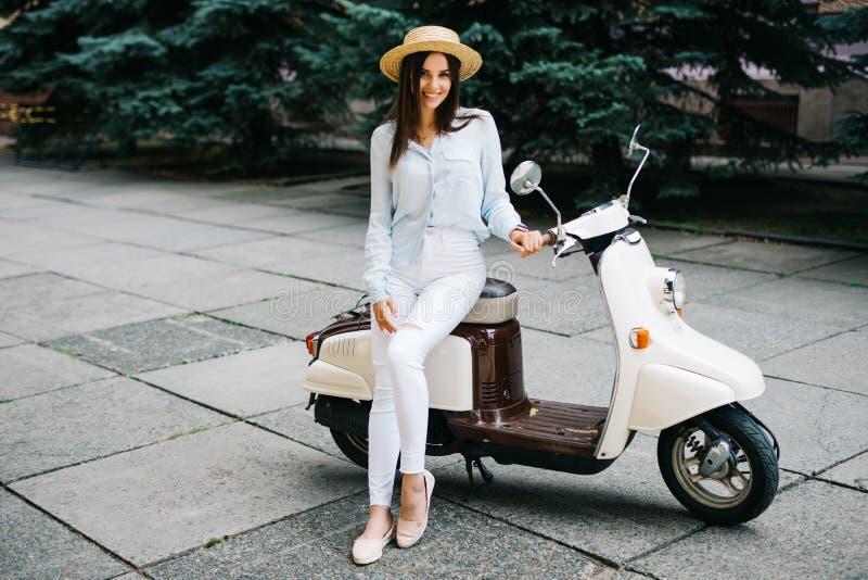 Sammanträde för ung kvinna på motosparkcykeln på den smala gatan i gammal stad royaltyfria bilder