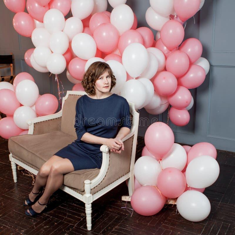 Sammanträde för ung kvinna på soffan i ett rum mycket royaltyfri bild