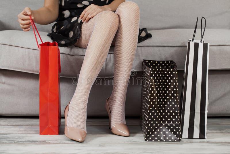 Sammanträde för ung kvinna på soffan med shoppingpåsar royaltyfri bild