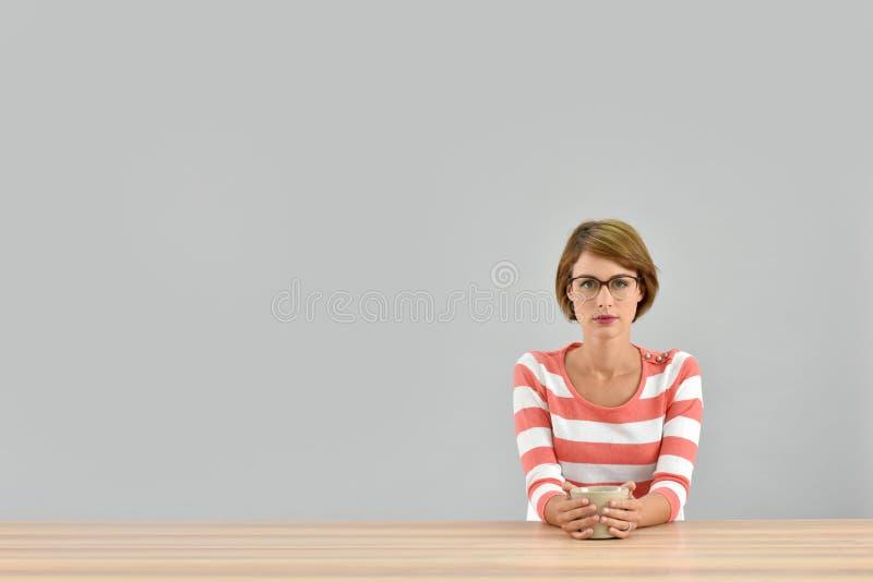 Sammanträde för ung kvinna på tabellen med den isolerade kopp te royaltyfri bild