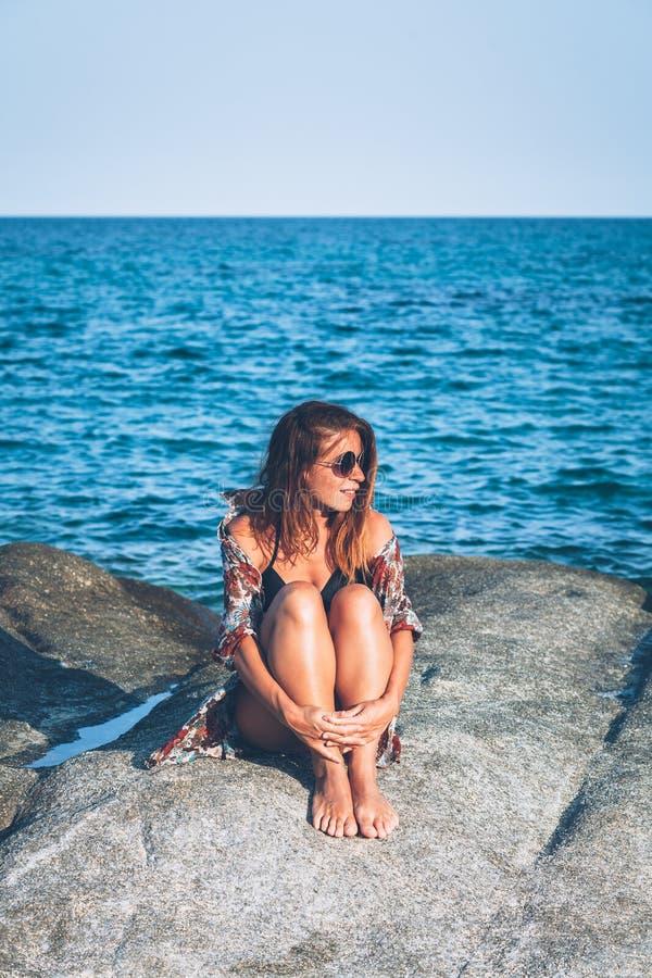 Sammanträde för ung kvinna på vagga som tycker om att solbada royaltyfri foto