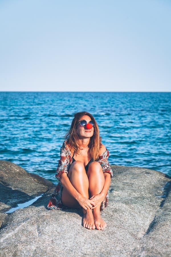 Sammanträde för ung kvinna på vagga som tycker om att solbada arkivfoton