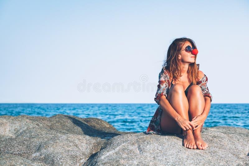 Sammanträde för ung kvinna på vagga som tycker om att solbada arkivfoto