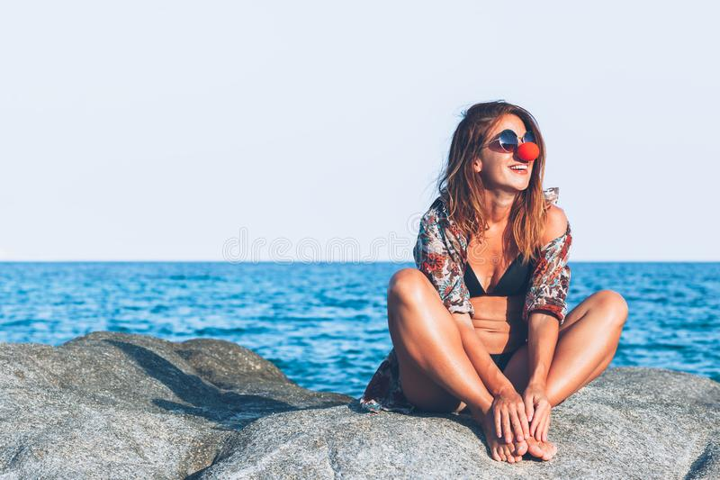 Sammanträde för ung kvinna på vagga som tycker om att solbada royaltyfria bilder
