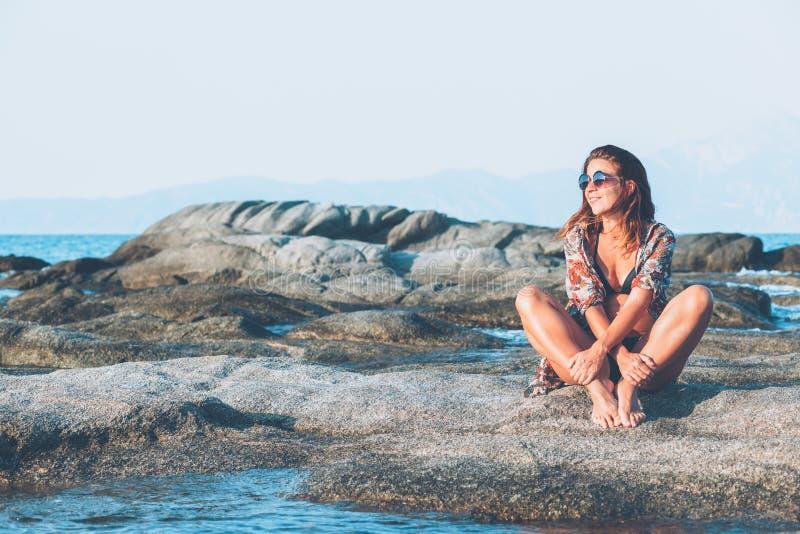 Sammanträde för ung kvinna på vagga som tycker om att solbada royaltyfria foton