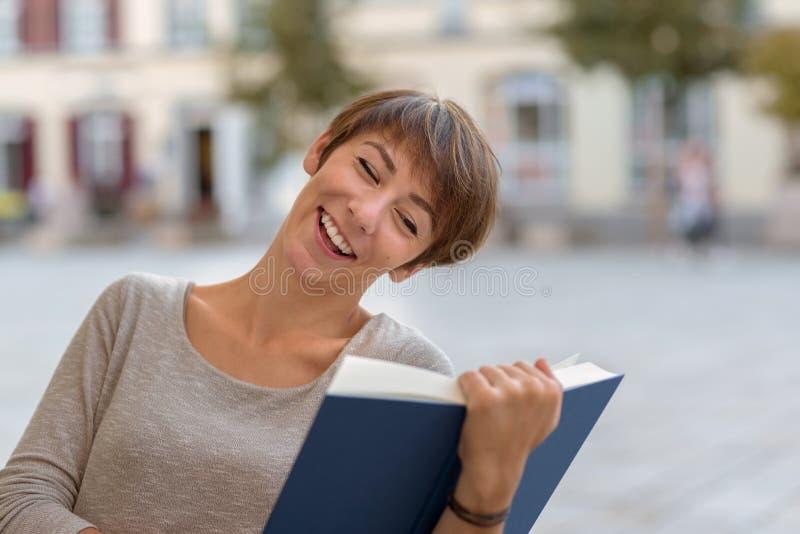 Sammanträde för ung kvinna som utomhus läser en bok royaltyfri foto