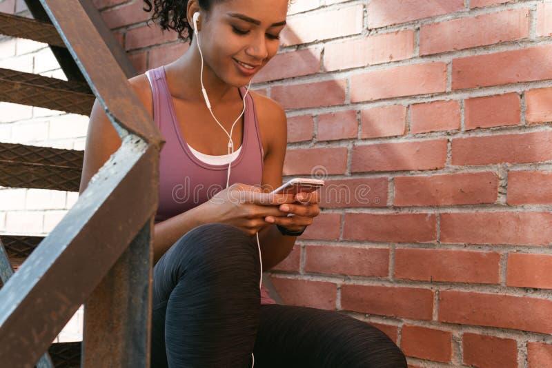 Sammanträde för ung kvinna utomhus och att smsa meddelandet arkivfoton