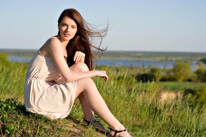 Sammanträde för ung kvinna vid en klippa med en trevlig sikt, bakom som han drar tillbaka royaltyfria bilder