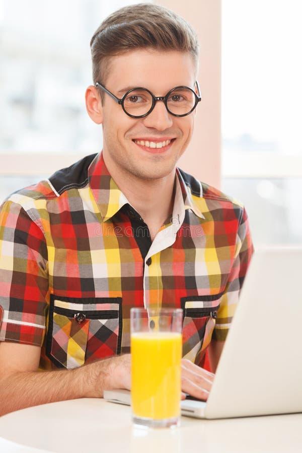 Sammanträde för ung man i kafé med bärbara datorn arkivfoton