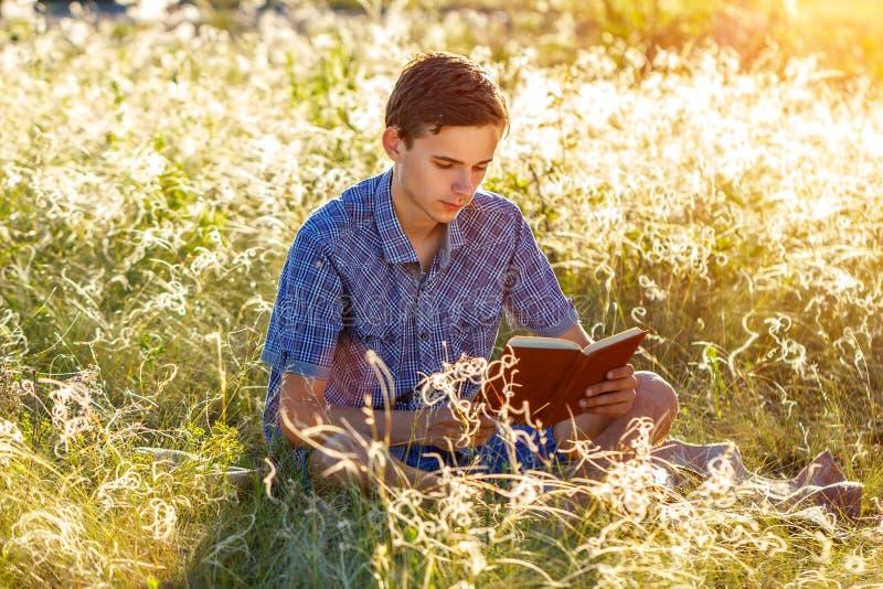 Sammanträde för ung man i naturen som läser en bok arkivfoto