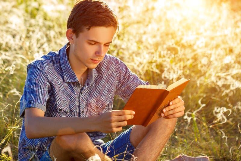 Sammanträde för ung man i naturen som läser en bok arkivfoton