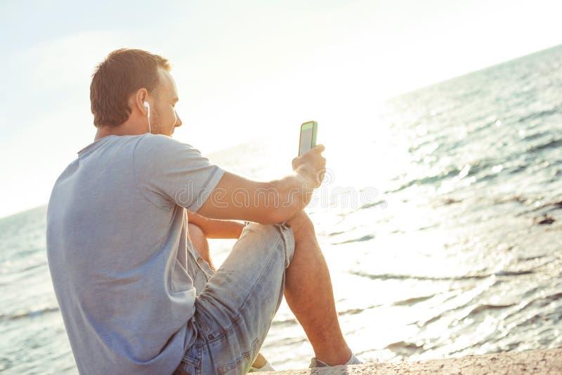 Sammanträde för ung man nära havet med mobiltelefonen arkivfoton