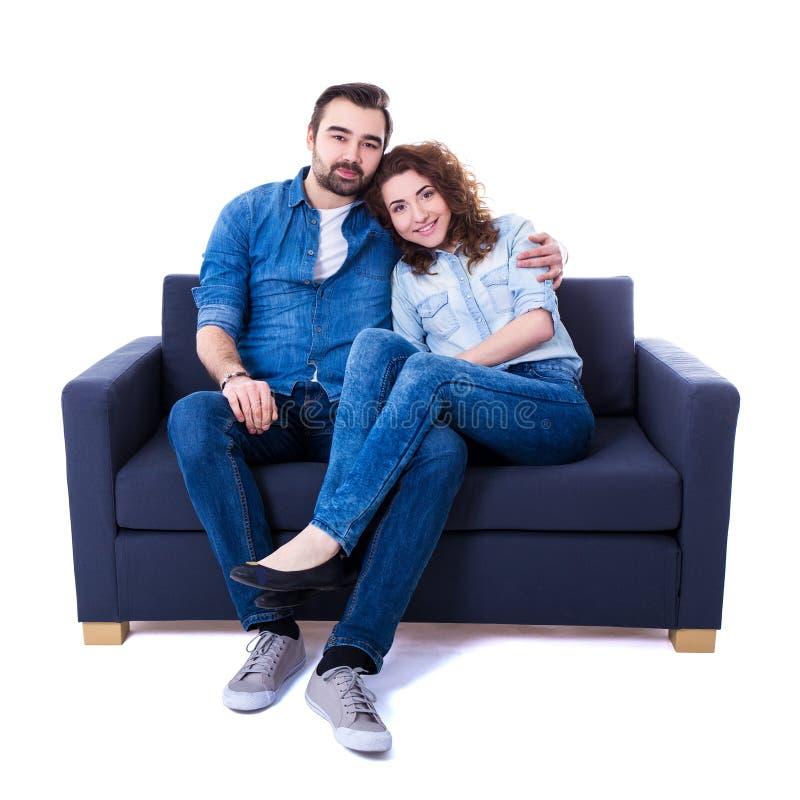 Sammanträde för ung man och kvinnapå soffan som isoleras på vit royaltyfri fotografi