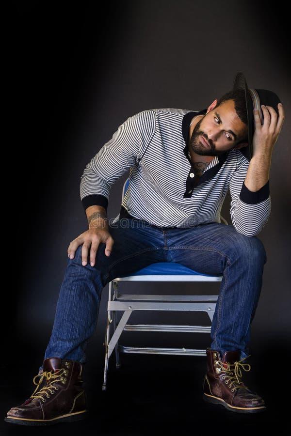 Sammanträde för ung man på en stol royaltyfria bilder