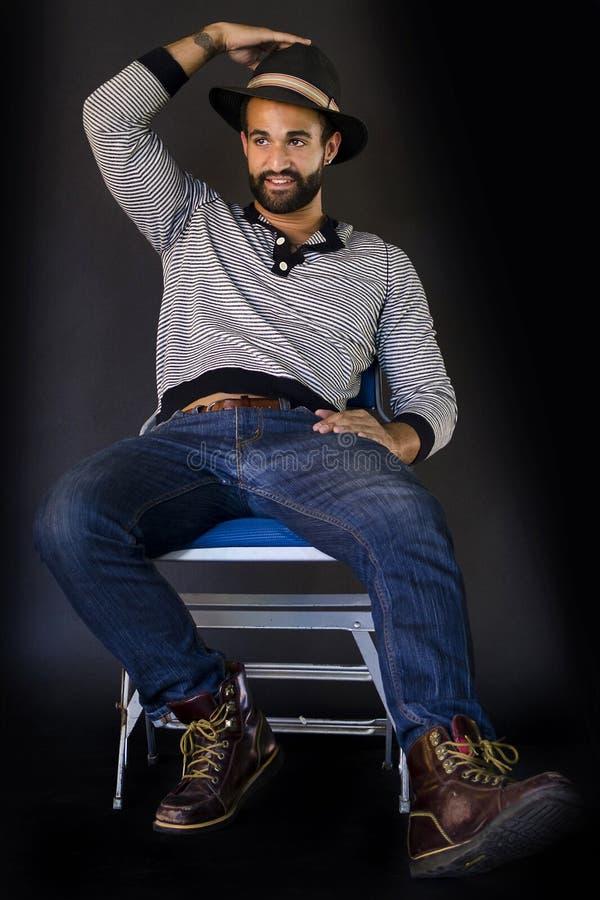 Sammanträde för ung man på en stol royaltyfri bild