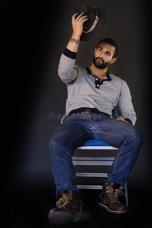 Sammanträde för ung man på en stol royaltyfri foto