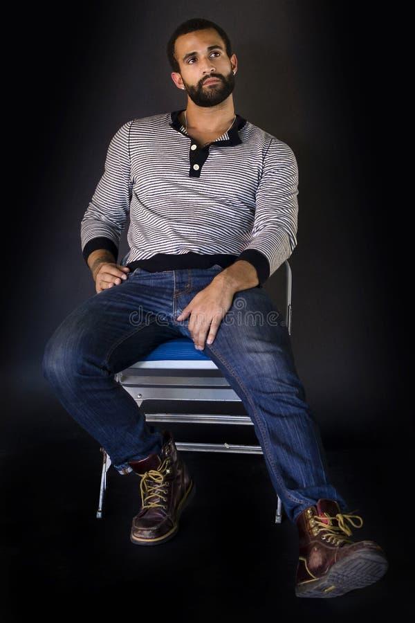 Sammanträde för ung man på en stol arkivbild