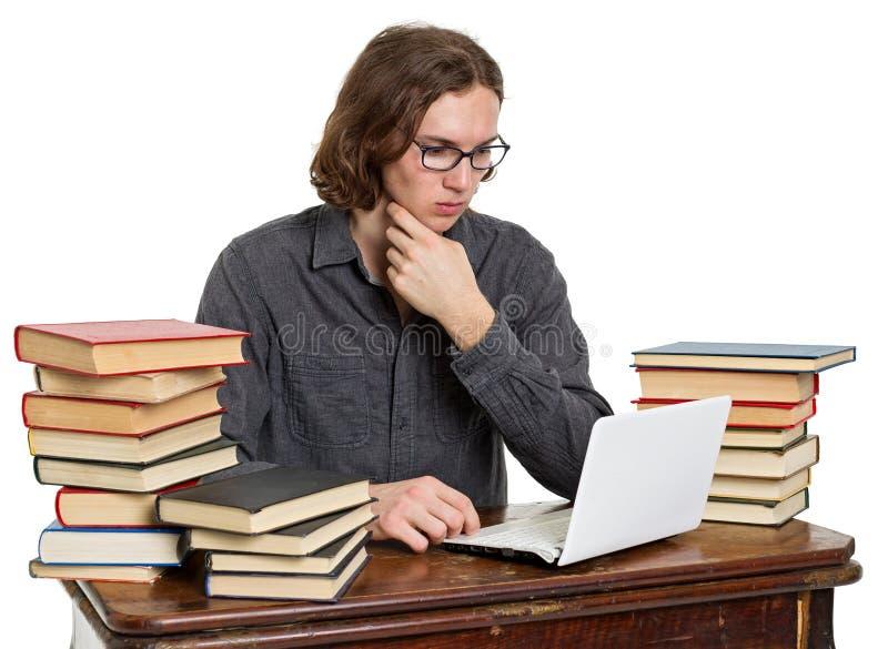 Sammanträde för ung man på en tabell med böcker och bärbara datorn royaltyfri bild
