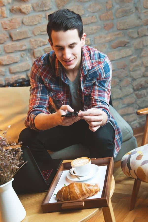 Sammanträde för ung man på ett kafé som tar ett kort av hans mat royaltyfri fotografi