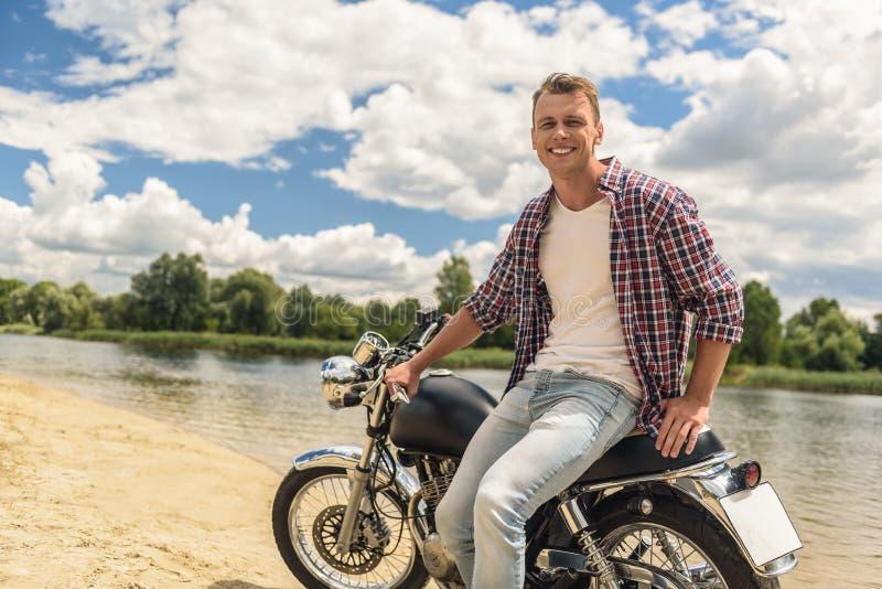 Sammanträde för ung man på hans moped royaltyfria foton