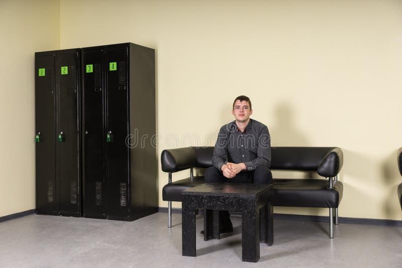 Sammanträde för ung man på läder Sofa Locker Room royaltyfria foton