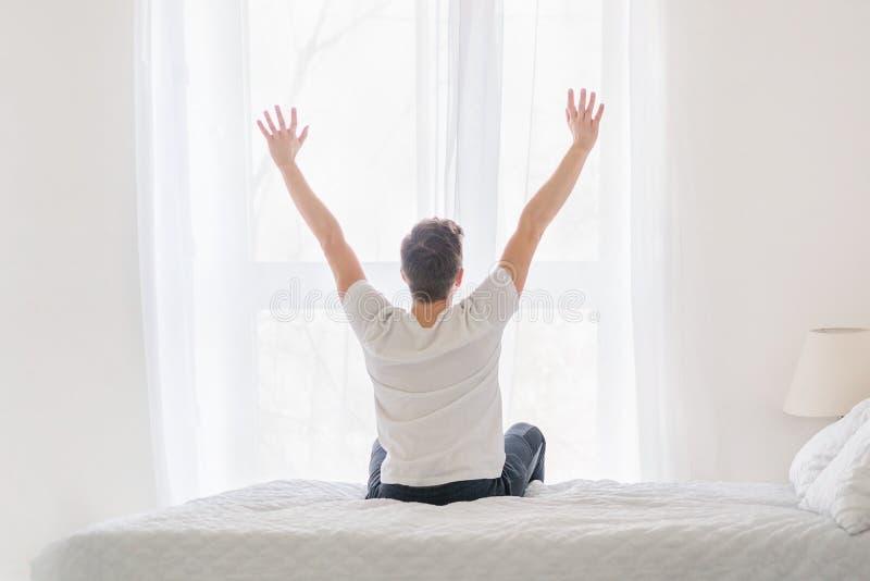 Sammanträde för ung man på säng med händer som lyfts upp royaltyfria foton