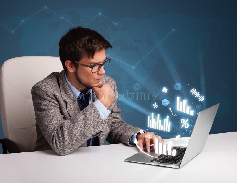Sammanträde för ung man på skrivbordet och maskinskrivning på bärbara datorn med diagram och fotografering för bildbyråer