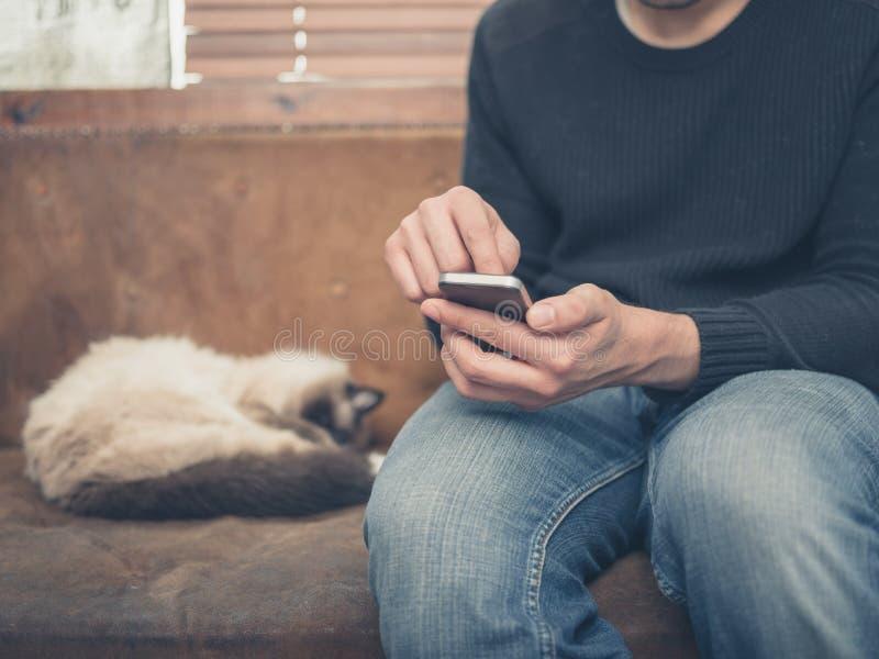 Sammanträde för ung man på soffan med katten genom att använda hans smartphone royaltyfri foto