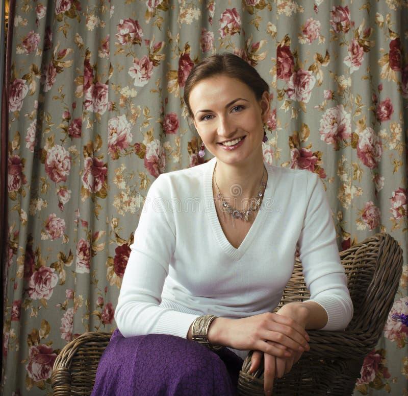 Sammanträde och le för mogen skönhetkvinna hemmastatt arkivfoton