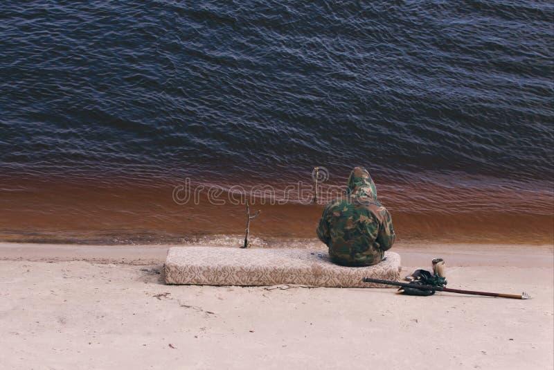 Sammanträdefiskaren med ett fångstredskap på sjön i kamouflagedräkt fotografering för bildbyråer