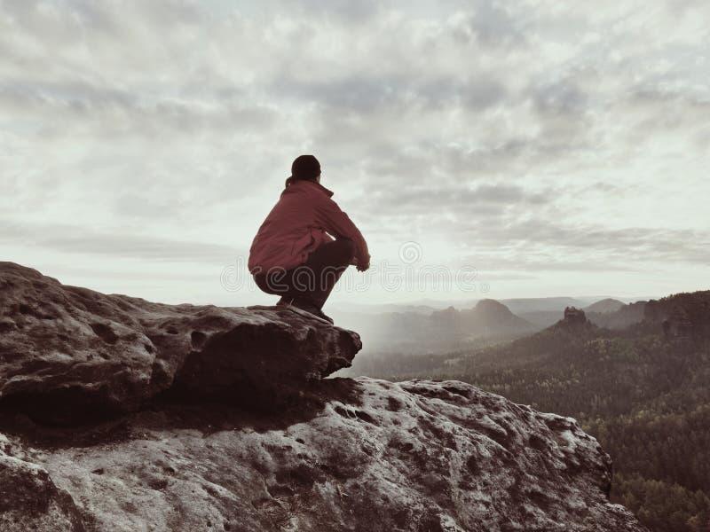 Sammanträdefotvandraren vaggar på Mannen i röd svart varm kläder sitter på klippan och tycker om avlägsen sikt royaltyfri foto