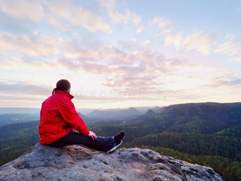 Sammanträdefotvandraren vaggar på Mannen i röd svart varm kläder sitter på klippan och tycker om avlägsen sikt fotografering för bildbyråer