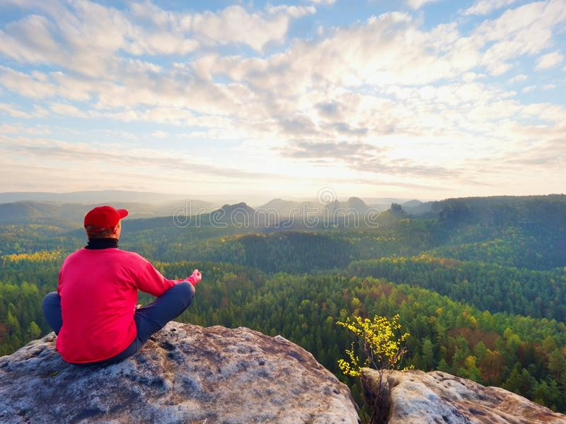 Sammanträdefotvandraren vaggar på Mannen i röd svart varm kläder sitter på klippan och tycker om avlägsen sikt arkivbilder