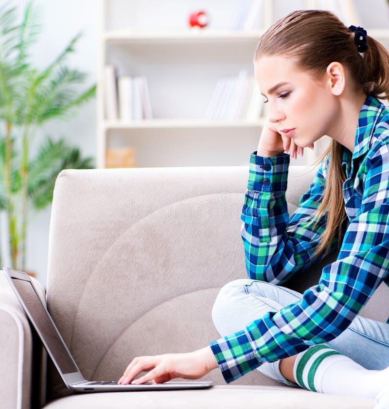 Sammantr?de f?r kvinnlig student p? soffan med b?rbara datorn arkivfoton
