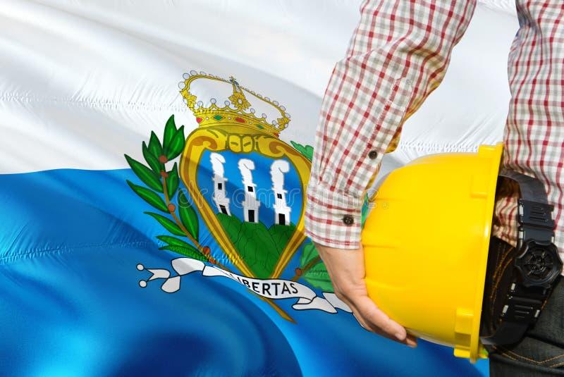 Sammarinese inżynier trzyma żółtego zbawczego hełm z machać San Marino flagi tło Budowy i budynku poj?cie fotografia royalty free