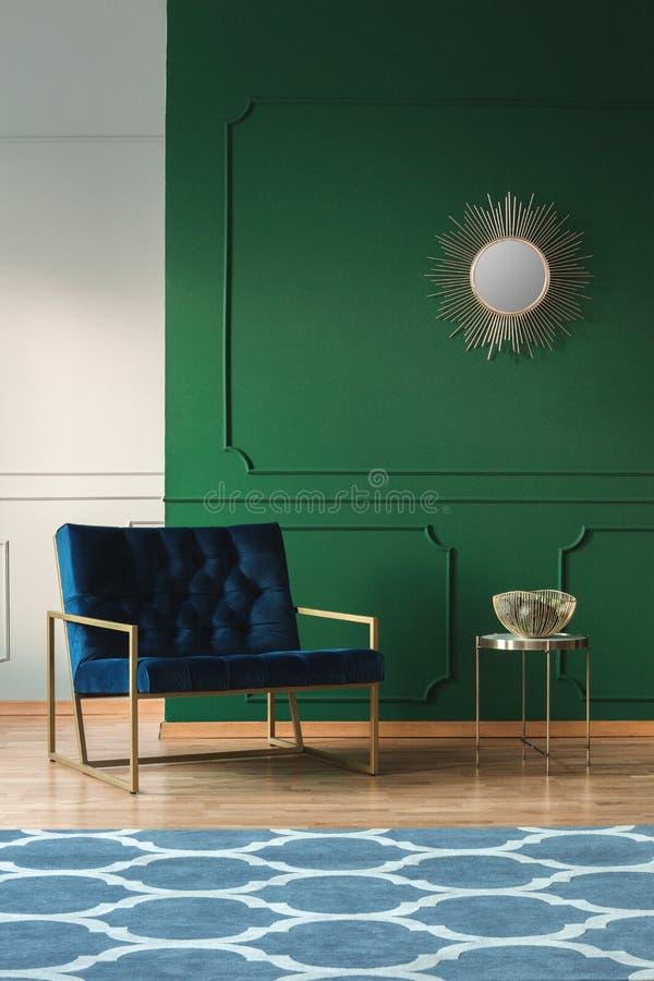 Sammetfåtölj i stilfull vardagsrum som är inre i moderiktig lägenhet arkivbild