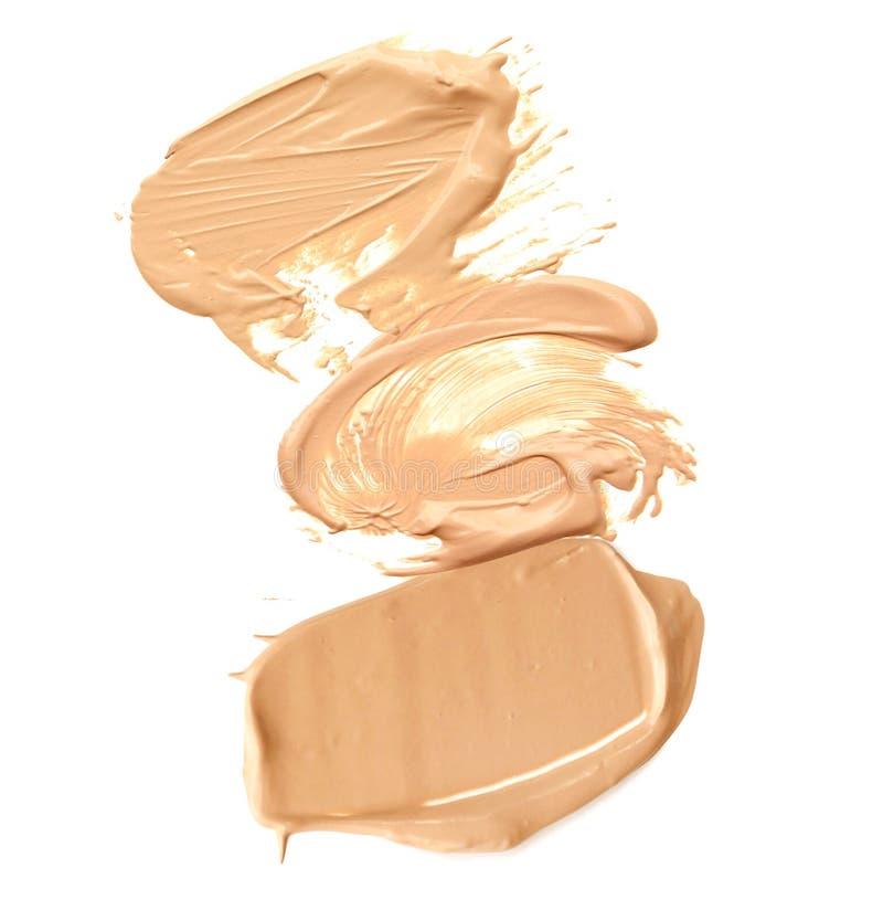 Sammlung des beige Abstrichs zerquetschte kosmetische Produkte auf einem weißen Hintergrund stockfotos