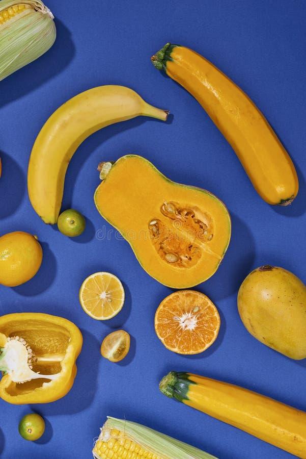 Sammlung frisches gelbes Obst und Gemüse auf dem blauen Hintergrund stockfotografie