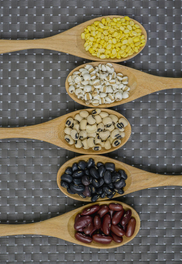 Sammlung Getreidekorn im hölzernen Löffel auf braunem Hintergrund lizenzfreie stockbilder